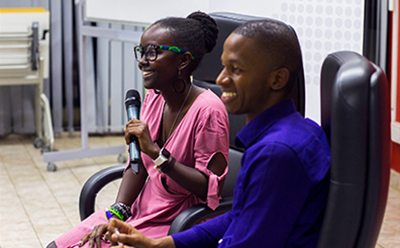 Photo of me and session host at the CMU Africa Alumni session laughing while holding microphone