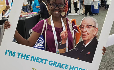 Photo of me holding a photo cut out prop (wearing a purple top with a multicolored beanie holding multiple prop bags) at the Grace Hopper 2018 event