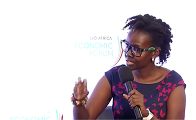 Photo of me at the Leo Africa Economic Forum speaking into a microphone, wearing blue dress with pink flowers and